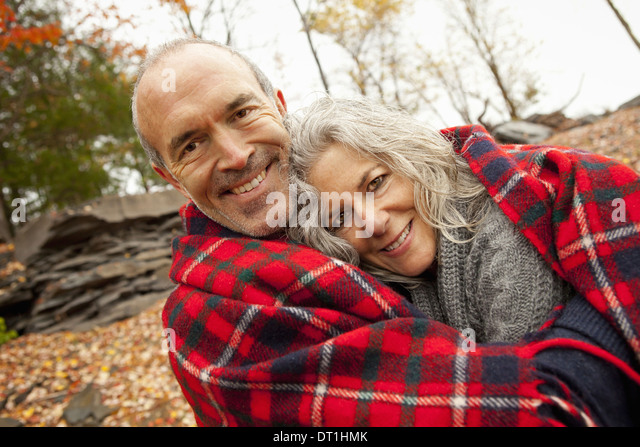 A couple man and woman on a day out in autumn Sharing a picnic rug to keep warm - Stock Image