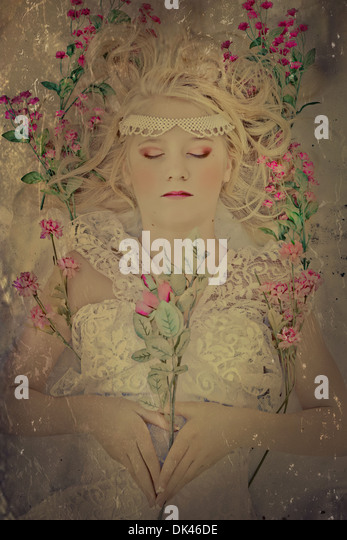 Beautiful blond woman in white lace dress asleep with flowers strewn around her - Stock-Bilder