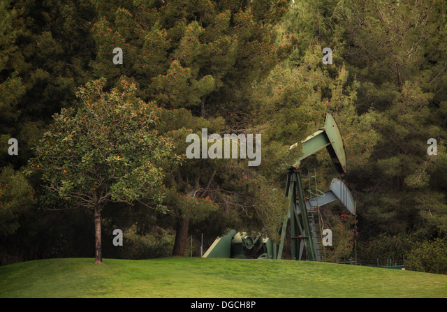 Derricks in oil well in countryside - Stock Image