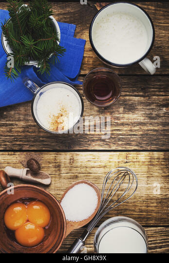 Eggnog  ingredients on rustic wooden table viewed from above.  Egg milk punch with raw egg yolks, milk, cream, sugar, - Stock Image