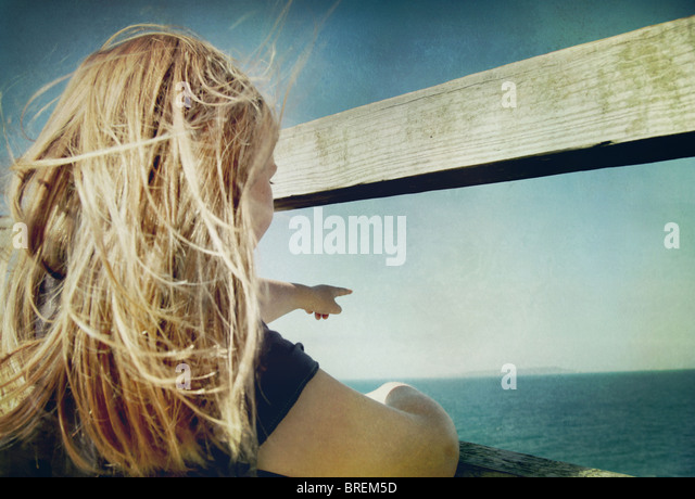 girl pointing out to sea - Stock-Bilder