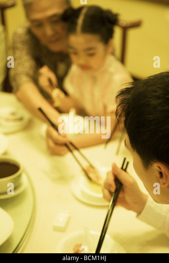 Famliy eating with chopsticks, cropped view - Stock Image