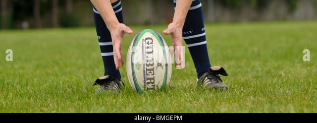 Rugby player places a Gilbert rugby ball on the ground ready for a spot kick, two hands are either side of the ball. - Stock Image