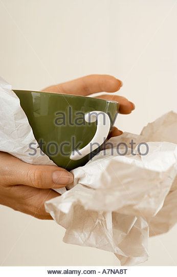Woman moving house wrapping crockery in paper side view close up of cup - Stock Image