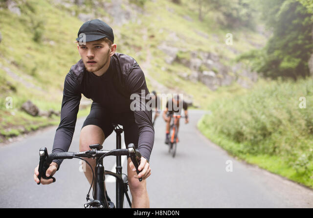A young cyclist is in the lead during a fun road race with friends - Stock-Bilder