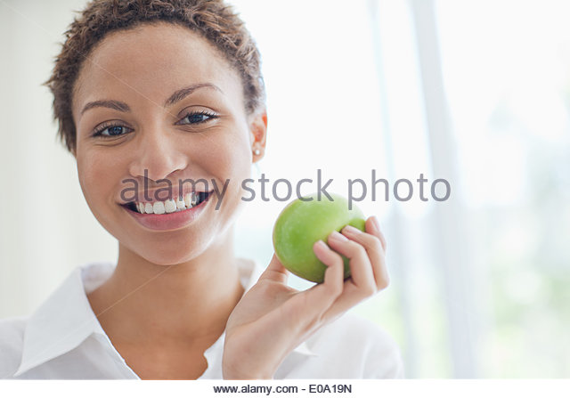 Woman eating green apple - Stock Image