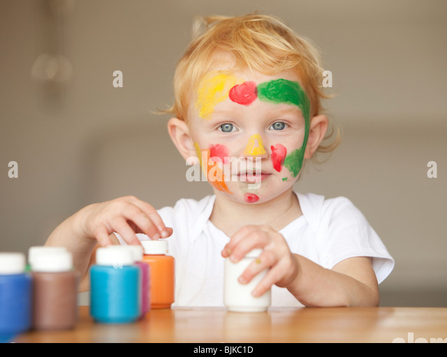 Little girl playing with finger paint - Stock Image