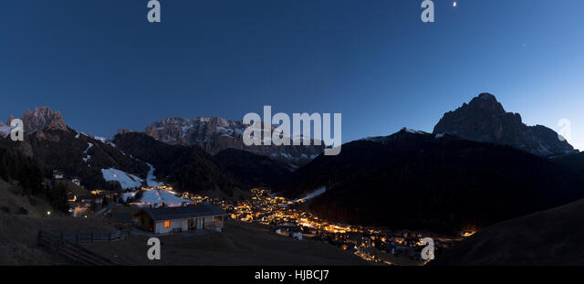 blue hour in Selva di Val Gardena with the moon above the Sassolungo Group profile - Stock Image