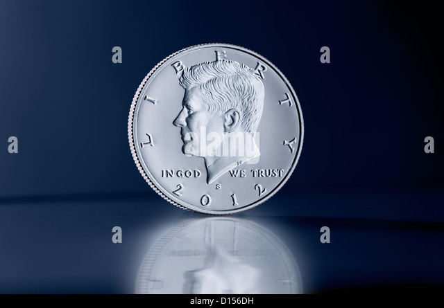 Upright Kennedy Half Dollar coin against dark background - Stock Image
