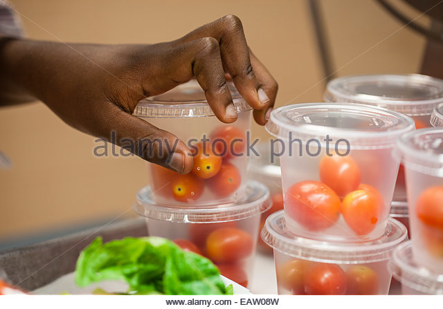 A child reaches for cherry tomatoes in an  elementary school cafeteria. - Stock Image
