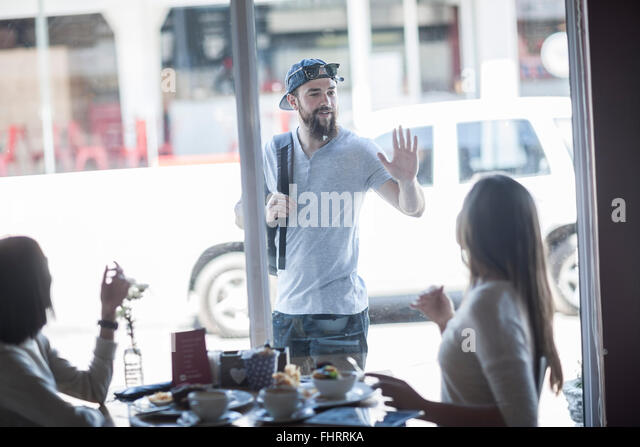 Portrait of young man greeting a friend from outside a coffee shop - Stock Image