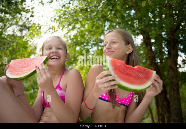 Friends eating watermelon in garden - Stock Image