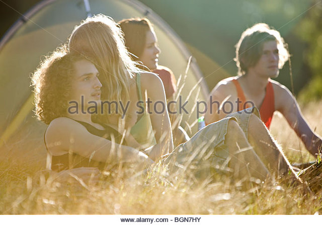 Two young couples sitting in front of a tent - Stock-Bilder