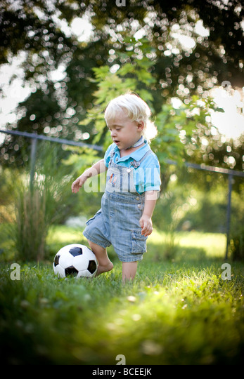 Toddler playing outdoors with a soccer ball - Stock Image