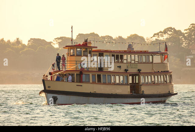 A bride and groom celebrate with their wedding party aboard an old wooden ferry on the harbour as the sun sets. - Stock Image