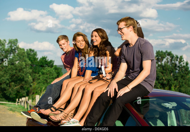 Five friends sitting on car roof - Stock Image