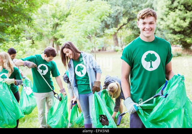 environmentalist volunteer picking up trash - Stock Image