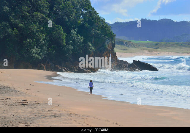 Woman walking along Hot Water Beach -Coromandel New Zealand , with the surf breaking on the beach beside her and - Stock Image