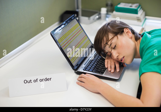 Businesswoman sleeping on 'out of order' laptop - Stock Image