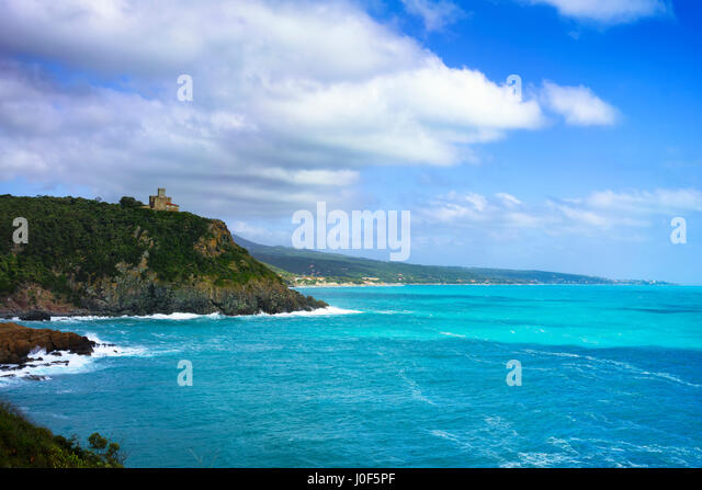 Cliff rock and building on the sea on sunset. Quercianella coast, Tuscany riviera, Italy, Europe. - Stock Image