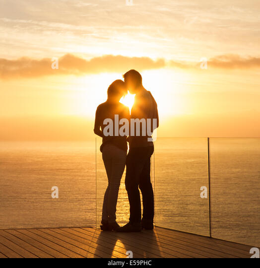 Silhouette of couple at sunset over ocean - Stock Image