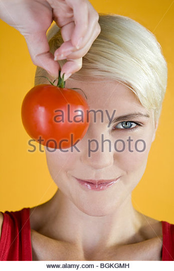 A Young Woman Holding A Tomato In Front Of Her Face - Stock Image