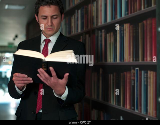 Businessman reading book in library - Stock-Bilder