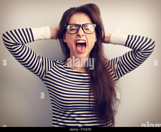 Angry young business woman in glasses strong screaming with wild open mouth and holding head the hands. Toned closeup - Stock Image
