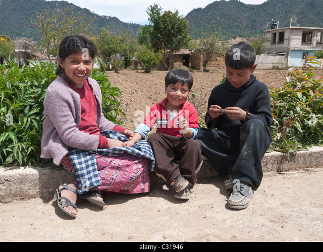 Three young Guatemalan children play on the side of a rural road near their home in Totonicapan, Guatemala. - Stock Image