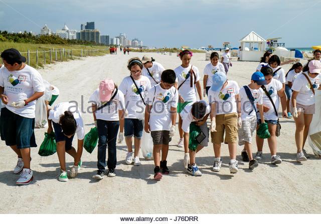 Miami Beach Florida Hands on Miami Beach Clean-up litter trash pollution environment sand volunteer student Hispanic - Stock Image