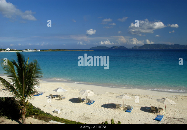 Anguilla beach Cap Juluca Beach umbrellas with St Martin in Background - Stock Image