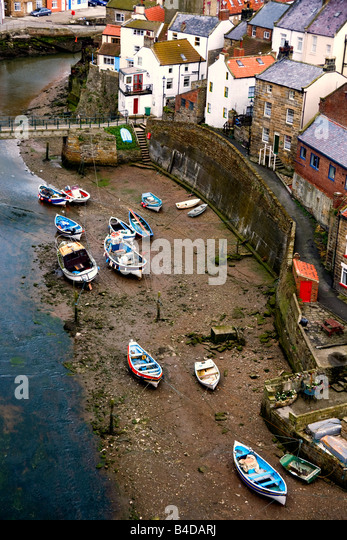 Boats beached on the riverbank, Staithes, North Yorkshire, England - Stock Image