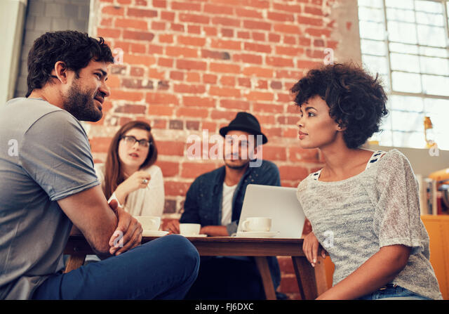 Portrait of young friends sitting at a cafe table and talking. Group of young people meeting at a coffee shop. - Stock Image
