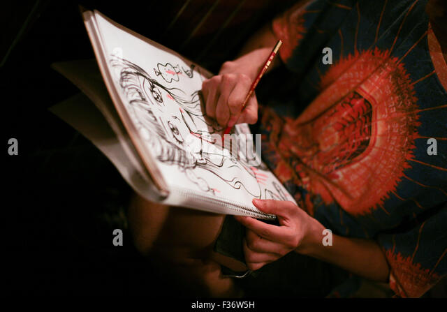 Artist illustrator drawing a picture with pen pencil - Stock Image
