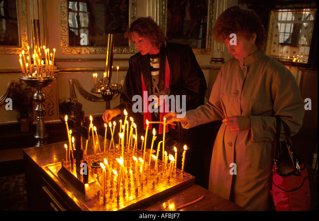 Latvia Riga Russian Orthodox Church women light candles - Stock Image