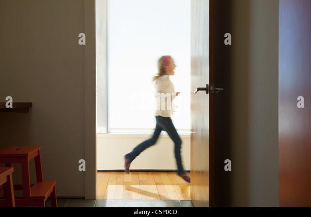 Girl running past doorway - Stock-Bilder