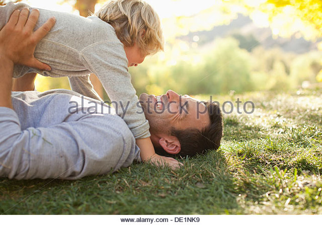 Father and son laying in grass together - Stock-Bilder