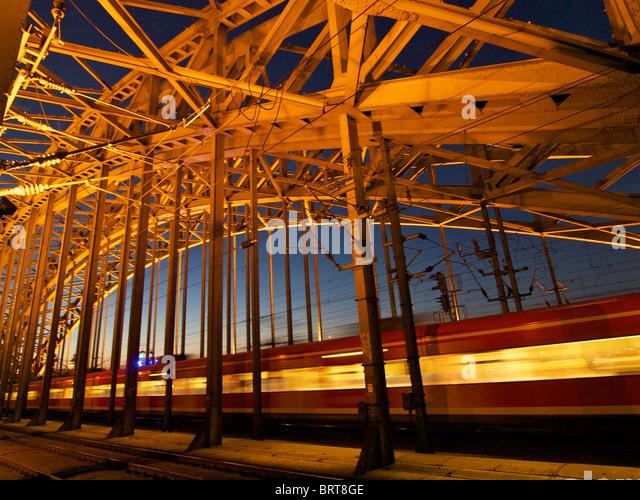 Train passing Hohenzollernbrucke railway bridge at night. Cologne, NRW, Germany - Stock Image