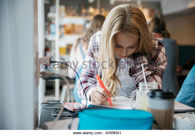 Focused Caucasian high school girl student studying in cafe - Stock Image