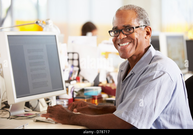 Man Working At Desk In Busy Creative Office - Stock Image