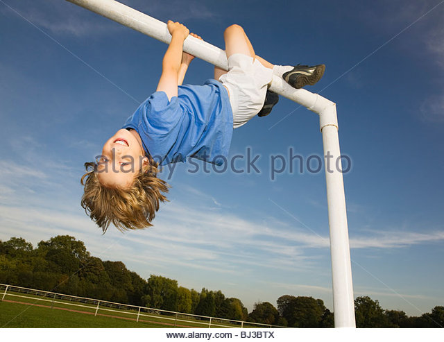 Boy hanging off goal post - Stock Image