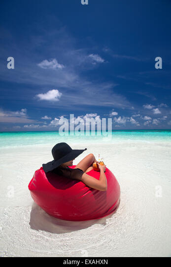 Woman relaxing on the beach, Maldives, Indian Ocean, Asia - Stock Image
