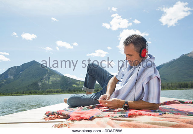Mature man listening to music on dock - Stock Image