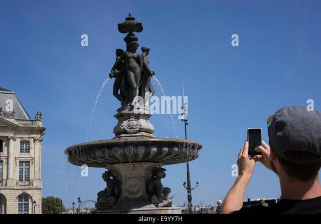 Man taking photograph, Place de la Bourse (Place Royale), Bordeaux, France - Stock Image