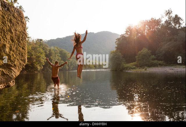Young couple jumping into river, Hamburg, Pennsylvania, USA - Stock-Bilder
