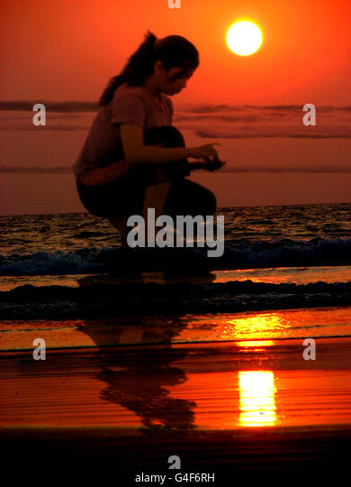 A teenage girl collecting shells on the beach - Stock Image