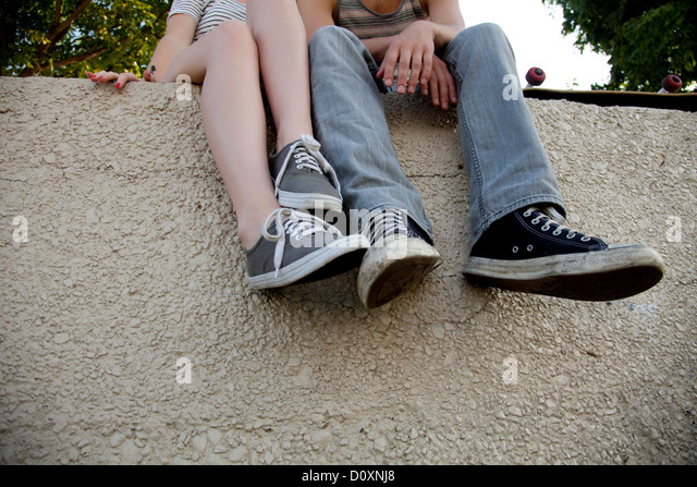 Young couple sitting on wall, low section - Stock-Bilder