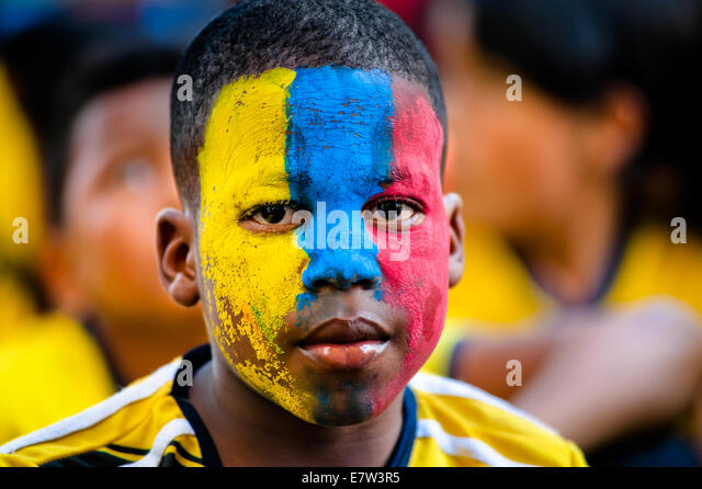 A Colombian boy watches the football match at the FIFA World Cup 2014, in a park in Cali, Colombia. - Stock Image