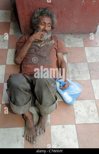 Nicaragua Granada Calle Real Xalteva vagrant homeless derelict poverty man dirty barefoot grimy lying on dirty floor - Stock Image