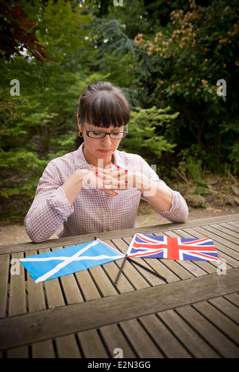 Young woman looking at a Scottish and British flag deciding how to vote in the Scottish independence referendum - Stock Image